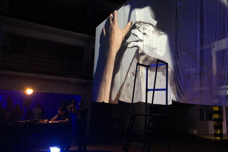 una tela bianca dove sono proiettate immagini una mano reale e una diseganta durante l'evento di Be Open a Dumbo
