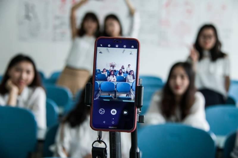Gruppo di ragazze che in una sala si fanno un selfie con smarphone